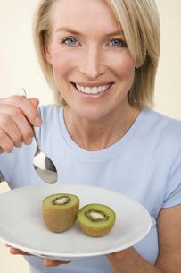 A woman eating a kiwi fruit.の写真素材 [FYI02246989]
