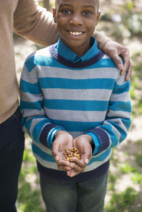 A mother and son, a boy holding a handful of nuts.の写真素材 [FYI02246998]