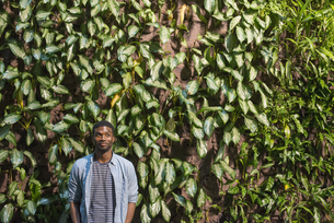 A man standing in front of a wall covered in plantsの写真素材 [FYI02247053]