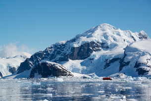 A small boat floating on the ocean among ice floes, off the shore of an island in Antarctica.の写真素材 [FYI02247055]