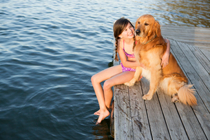 A girl and her golden retriever dog seated on a jetty by a lake.の写真素材 [FYI02247064]