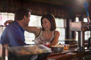 A man and woman seated at a bar, flirting and talking. On a date.の写真素材 [FYI02247073]