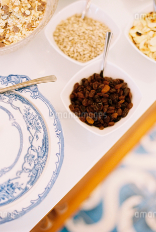 A tabletop with a blue and white plate, bowls of granola, oats and raisins.の写真素材 [FYI02247078]