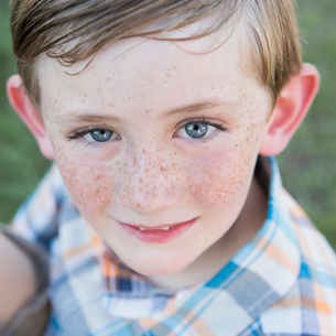 Portrait of a young boy with blue eyes and freckles on his nose.の写真素材 [FYI02247084]