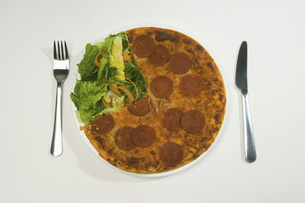 A salami pizza and salad on a plate.の写真素材 [FYI02247108]