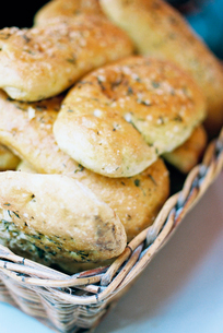 Bread rolls with seeds on the top, in a basket on a table.の写真素材 [FYI02247113]
