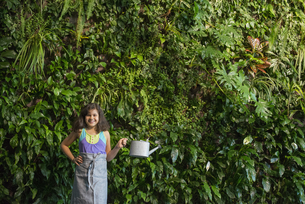 A young girl standing by wall covered with plants.の写真素材 [FYI02247210]