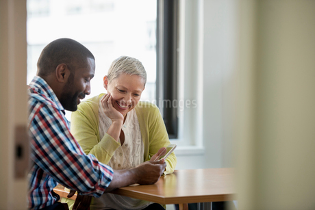 A man and woman in an office, sharing a digital tablet.の写真素材 [FYI02247230]