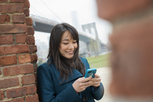 woman leaning against a brick wall, checking her phone.の写真素材 [FYI02247233]