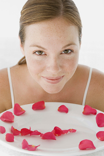 A spa treatment centre. A young woman with a white dish of pink rose petals.の写真素材 [FYI02247256]
