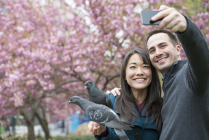 man and woman in park, taking selfy, pigeons on her wrist.の写真素材 [FYI02247269]