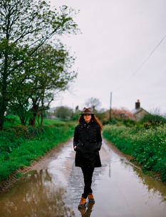 A woman walking on a wet road, wearing a coat and hat.の写真素材 [FYI02247281]