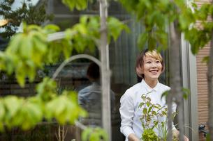 A woman standing in her garden.の写真素材 [FYI02247354]