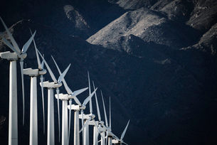 White wind turbines, in a row, against the backdrop of a snow capped mountain.の写真素材 [FYI02247365]
