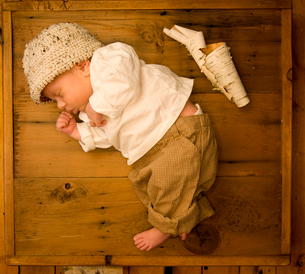 A newborn baby lying asleep on his side in a wooden box, with a scroll of white tree bark beside himの写真素材 [FYI02247386]