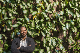 A man standing with folded arms, by a wall of foliage.の写真素材 [FYI02247390]