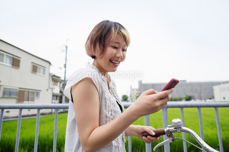 A woman pushing a bicycle while looking at her cell phone.の写真素材 [FYI02247415]