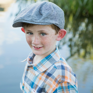 A young boy wearing a checked shirt and cloth cap with a large brim standing on a riverbank.の写真素材 [FYI02247422]