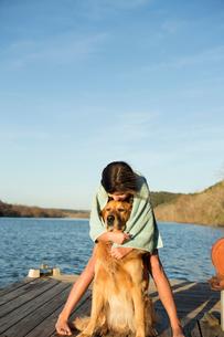 A girl cuddling a golden retriever dog.の写真素材 [FYI02247432]