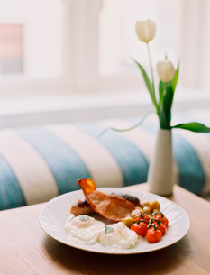 A plate of bacon and eggs, a full English breakfast on a table. A vase with white tulips.の写真素材 [FYI02247433]