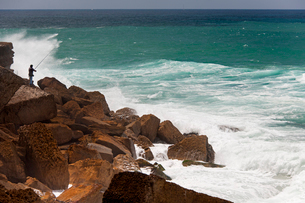 A fisherman standing on the rocks surf casting in the white waves on the Antlantic coast.の写真素材 [FYI02247477]
