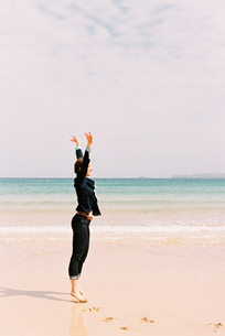 A woman standing barefoot on the sand raising her arms above her head, in a gesture.の写真素材 [FYI02247505]