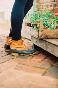 A woman wearing waterproof boots, with a box of seedlings.の写真素材 [FYI02247507]