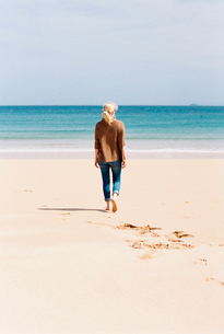 A woman walking barefoot on a beach, leaving footprints in the sand.の写真素材 [FYI02247535]