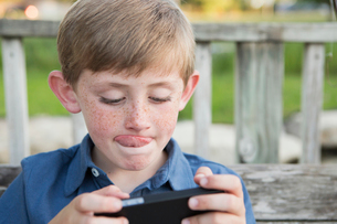 A young boy using a hand held electronic tablet or game and concentrating, sticking his tongue out.の写真素材 [FYI02247546]