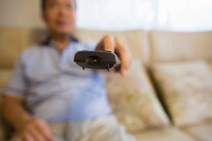 Man sitting on sofa holding remote control.の写真素材 [FYI02247566]