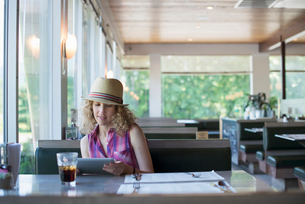 A woman in a hat sitting in a diner, holding a digital tablet, looking at the screen.の写真素材 [FYI02247585]