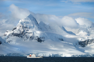 A ship under the towering shape of a mountain range.の写真素材 [FYI02247631]