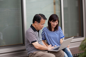 A man and a women sitting outside a house. Holding a laptop computer.の写真素材 [FYI02247644]
