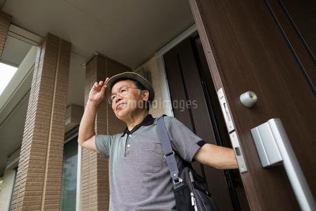 A man standing at his front door.の写真素材 [FYI02247661]