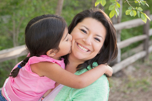 A mother in the park with her daughter, laughing and kissing each other.の写真素材 [FYI02247675]