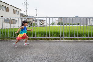 A young girl running along a footpath.の写真素材 [FYI02247680]