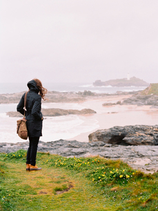 A woman lookng over the rocks and the shoreline on a windy day by the sea.の写真素材 [FYI02247681]