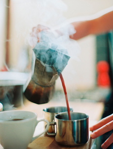 A person holding a coffee perculator and pouring hot coffee into cups.の写真素材 [FYI02247703]