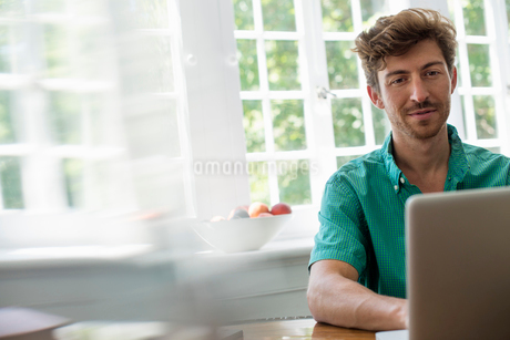 A man seated at a table using a laptop. Working from home.の写真素材 [FYI02247742]