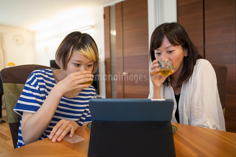 A woman sitting at a table with a laptop computer.の写真素材 [FYI02247763]