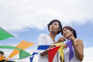 A couple, a man and woman in a Kyoto park holding up a colourful row of flags.の写真素材 [FYI02247776]