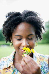 Portrait of a woman holding a yellow flower.の写真素材 [FYI02247782]