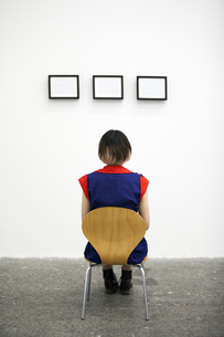An artist sitting on a chair, looking at an artwork.の写真素材 [FYI02247795]