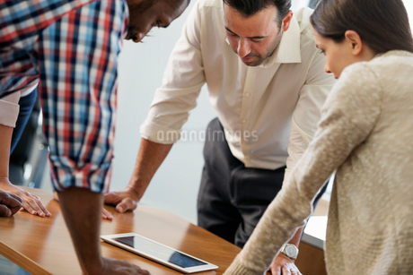 Four people leaning on a table at a meeting, looking at a digital tablet.の写真素材 [FYI02247852]