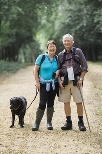 A mature couple hiking with their dog.の写真素材 [FYI02247856]