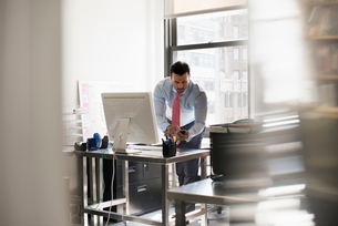 A man standing at his desk using his phone, dialling or texting.の写真素材 [FYI02247873]