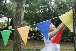 A woman in a Kyoto park holding up a colourful row of flags.の写真素材 [FYI02247877]