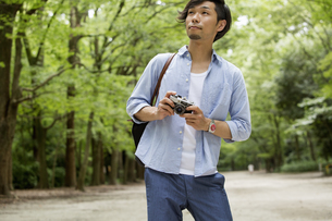 A man in a Kyoto park holding a camera.の写真素材 [FYI02247879]
