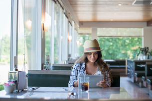 A young woman seated at a table in a diner, wearing a straw hat Using a digital tablet.の写真素材 [FYI02247889]