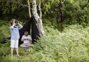 Two boys camping in New Forest. One sitting under a black canvas shelter.  One boy looking through bの写真素材 [FYI02247891]